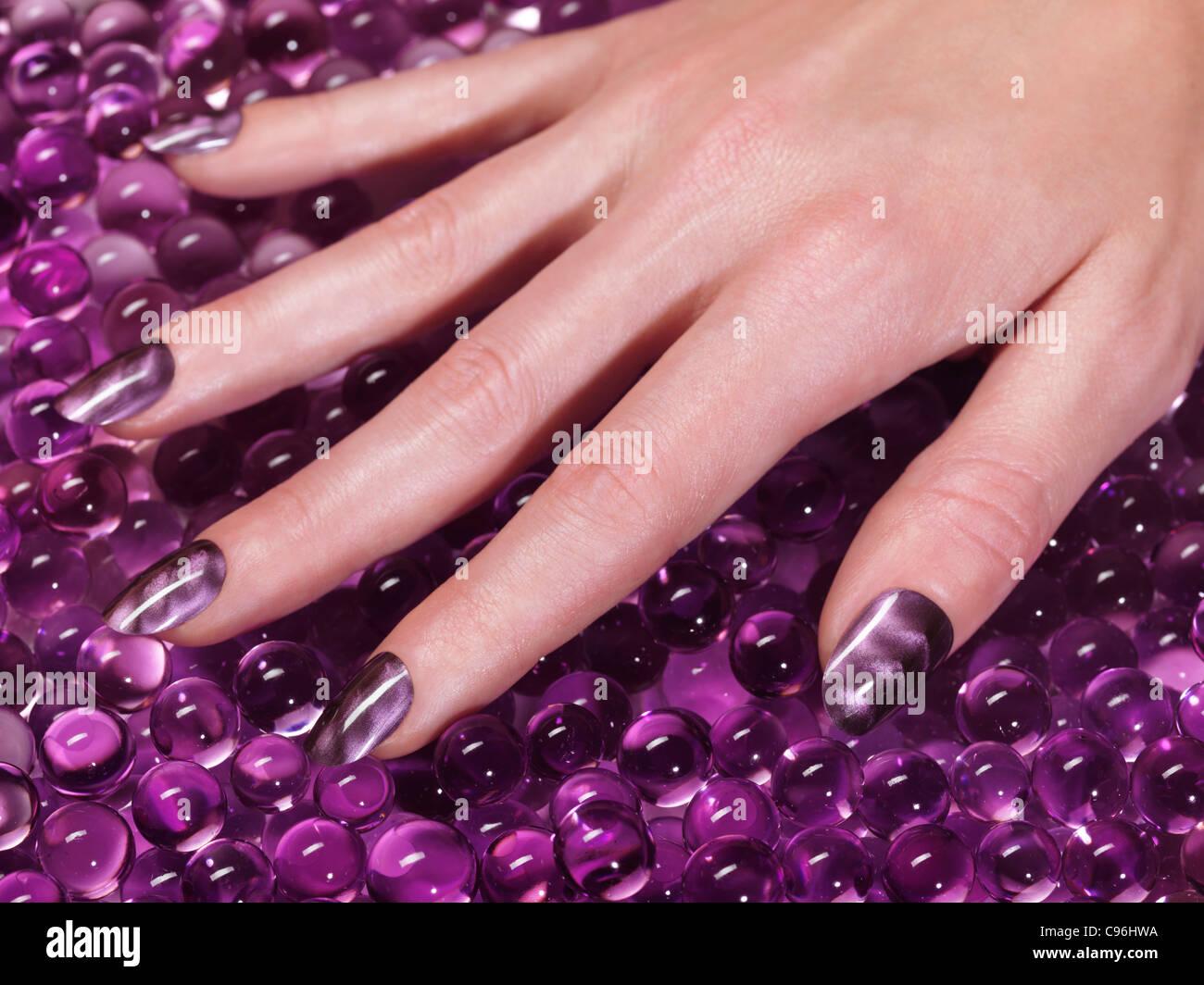 Primo piano della donna mano con le unghie acriliche e viola smalto per unghie Immagini Stock