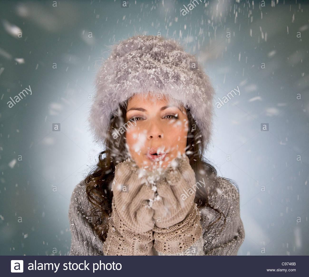 Una giovane donna di fiocchi di neve di soffiatura Immagini Stock