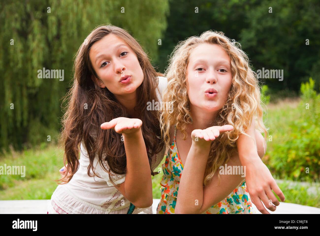 Due ragazze adolescenti ingannare intorno al paesaggio e baci di soffiatura Immagini Stock