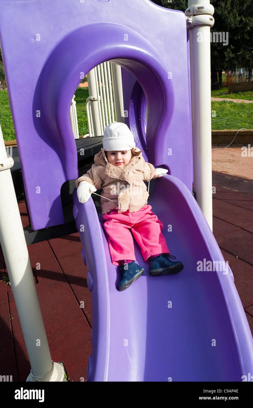 Bambino gioca su un parco giochi slitta Immagini Stock