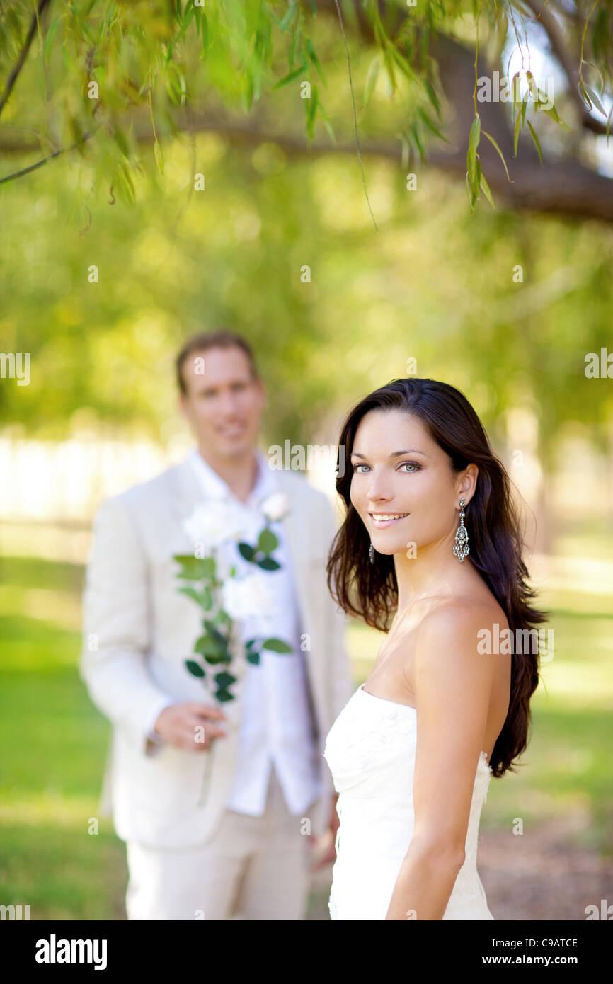 Coppia appena sposata con uomo con fiori in mano Immagini Stock