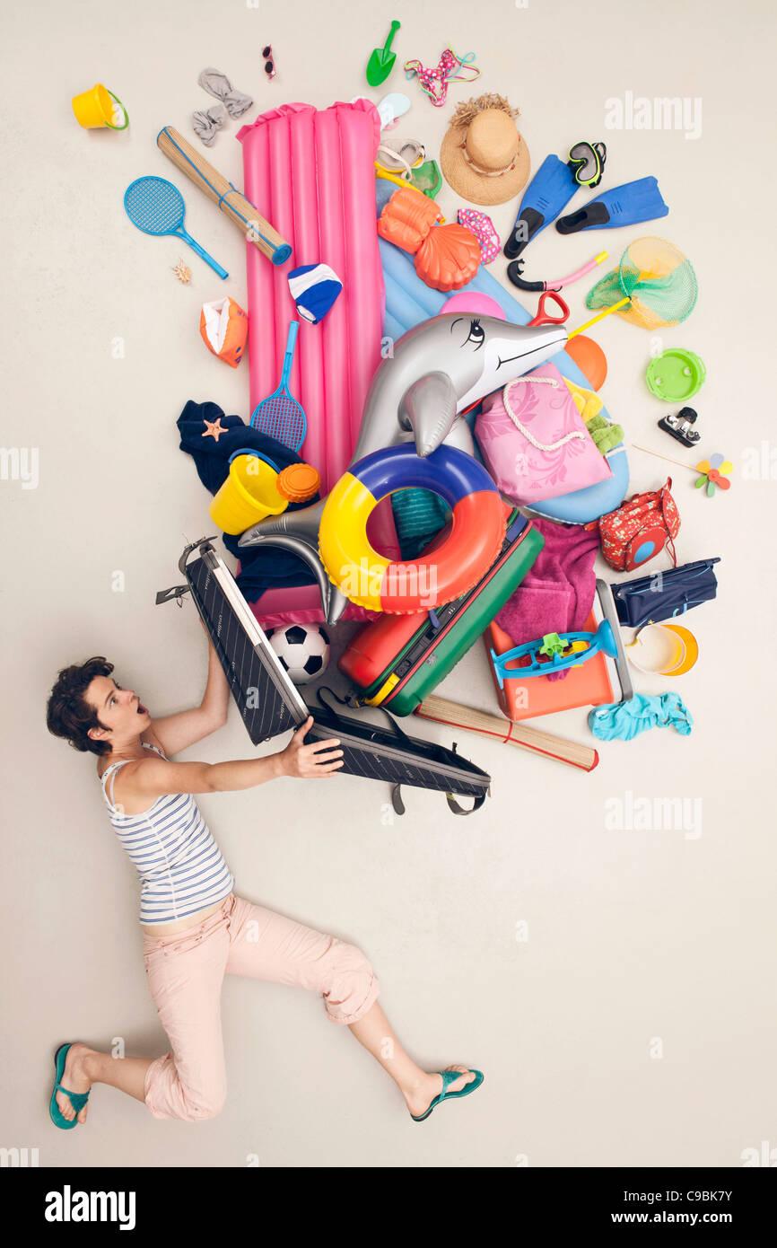 Germania, scena artificiale con donna bagaglio di apertura piena di giocattoli da spiaggia Immagini Stock