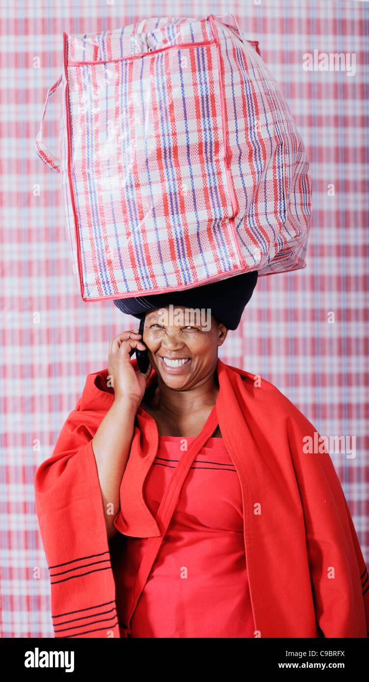 Donna in costume tradizionale la sacca di custodia su utilizzando il telefono cellulare e il Cape Town, Provincia Immagini Stock