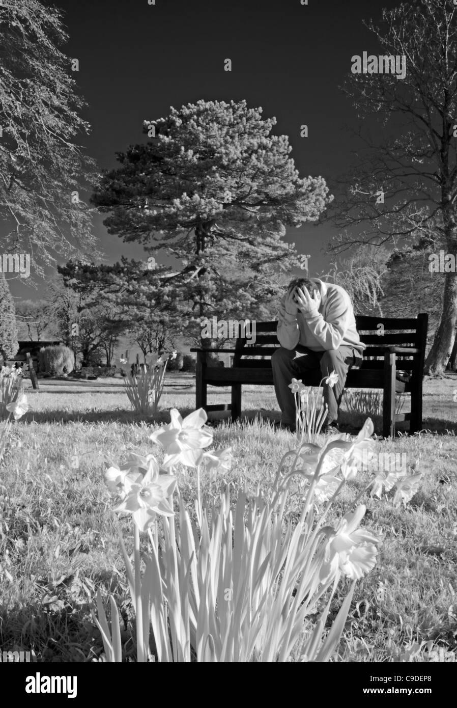 Maschio solitario della depressione nella primavera seduto su una panchina nel parco con testa in mani Immagini Stock