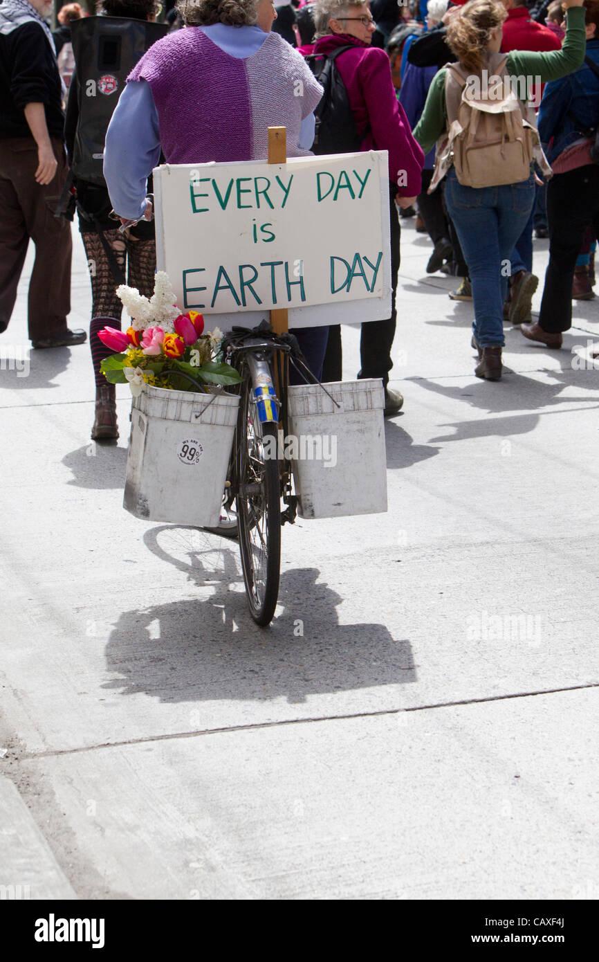 Manifestanti marciano e il ciclista con la Giornata della Terra segno, giorno di maggio Rally, 1 maggio, 2012, Seattle, Immagini Stock