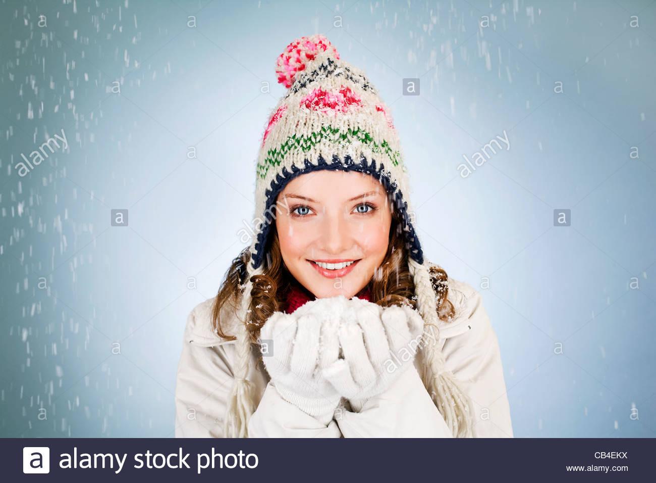 Una giovane donna in possesso di una manciata di neve, sorridente Immagini Stock