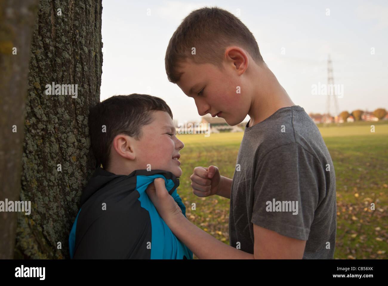 Un vecchio ragazzo bullismo un giovane ragazzo con il suo pugno azienda ribattuto lui fino contro un albero. Immagini Stock