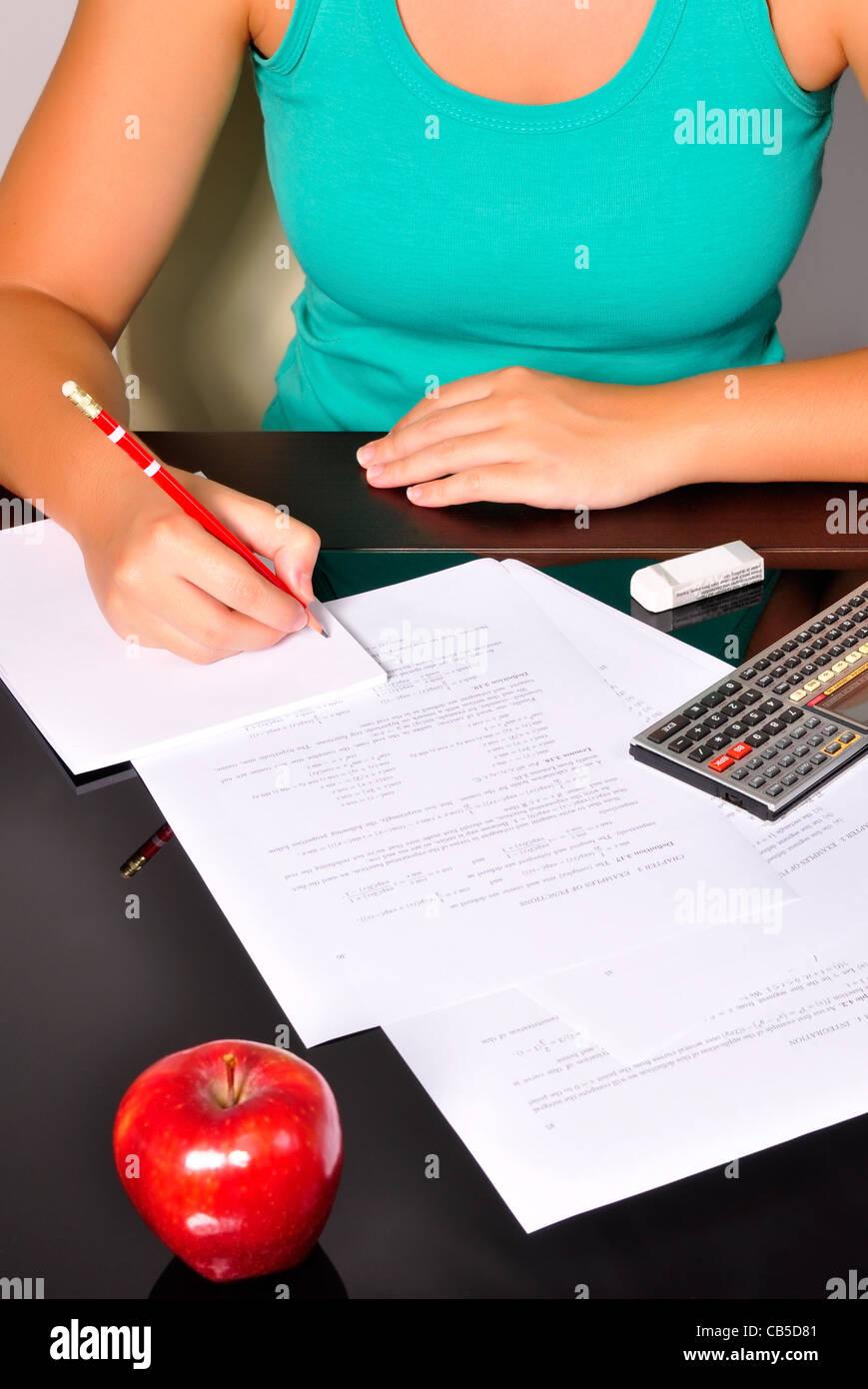 Studente facendo esercizi di matematica con una calcolatrice e una matita rossa. Immagini Stock