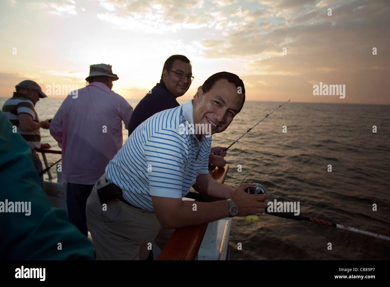 Il team di padre e figlio Luis Montes, Sr., destra e Luis Montes, Jr., sinistra, stand su un party barca da pesca Foto Stock
