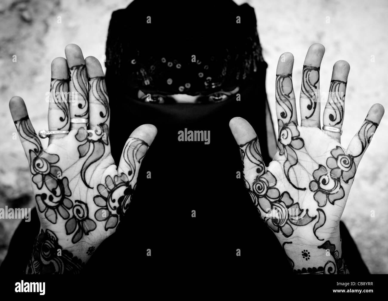 Irriconoscibile giovane donna indossa Hijab velo mostra il palmo della Sua mano dipinta con Henna e blu indaco, Immagini Stock