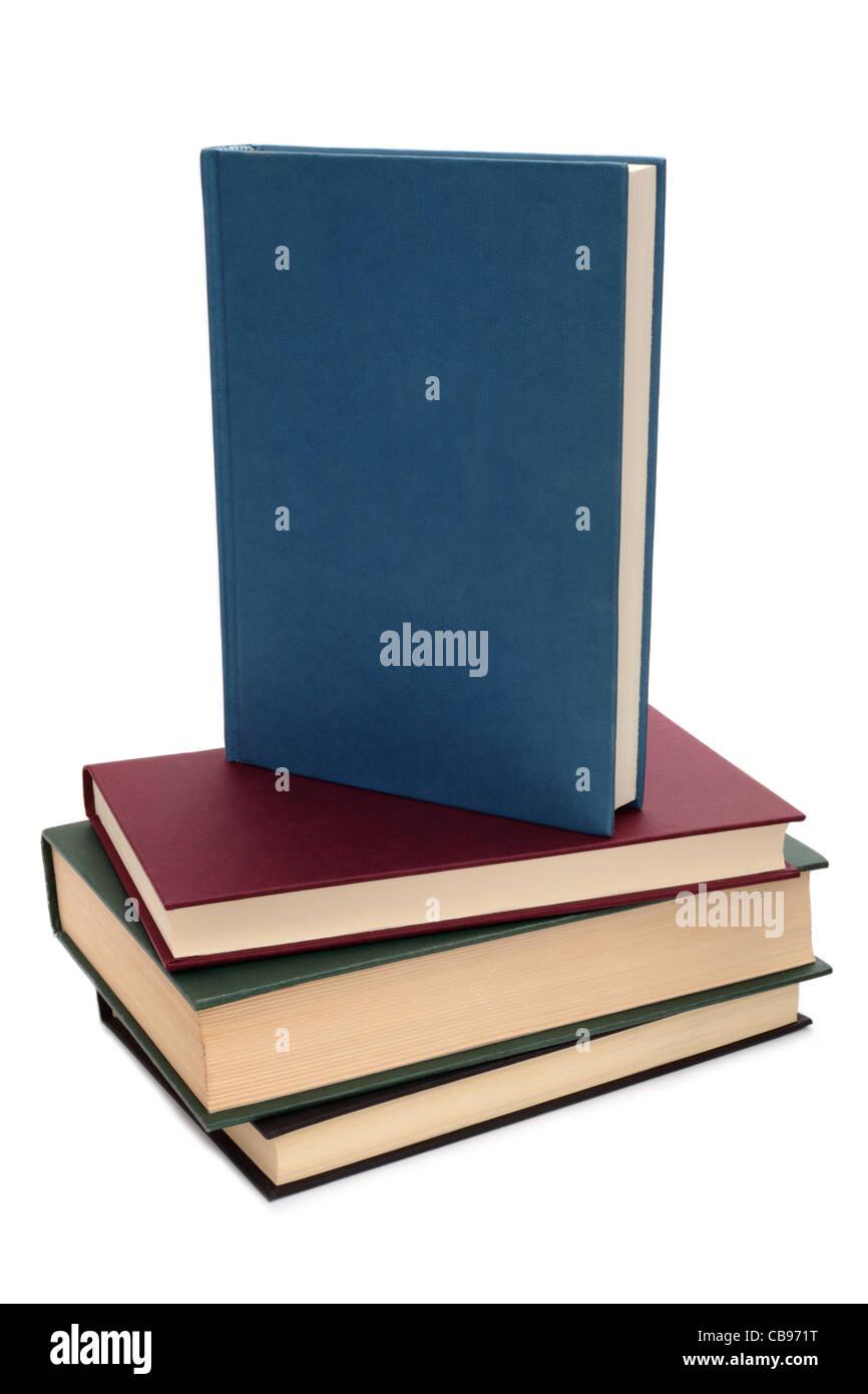 Una pila di libri con un libro sulla parte superiore che mostra un fustellato copertura blu. Immagini Stock