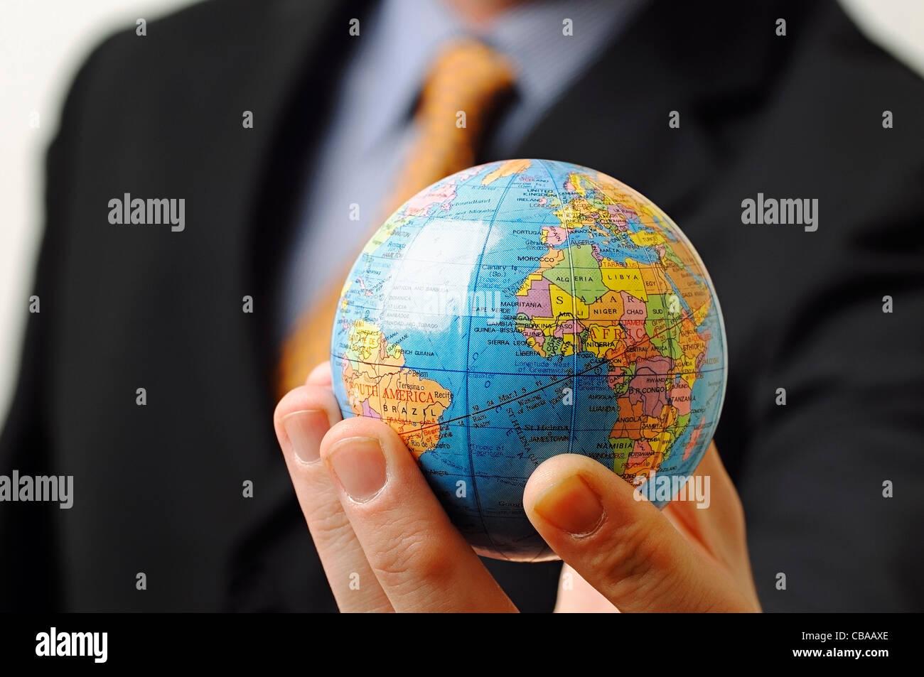 Imprenditore tenendo un globo in mano, vicino. Immagini Stock