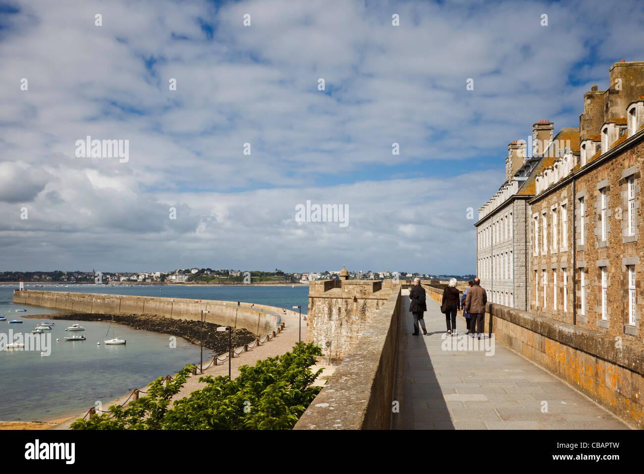 St Malo, Brittany, Francia - i turisti a piedi lungo le mura della città Immagini Stock