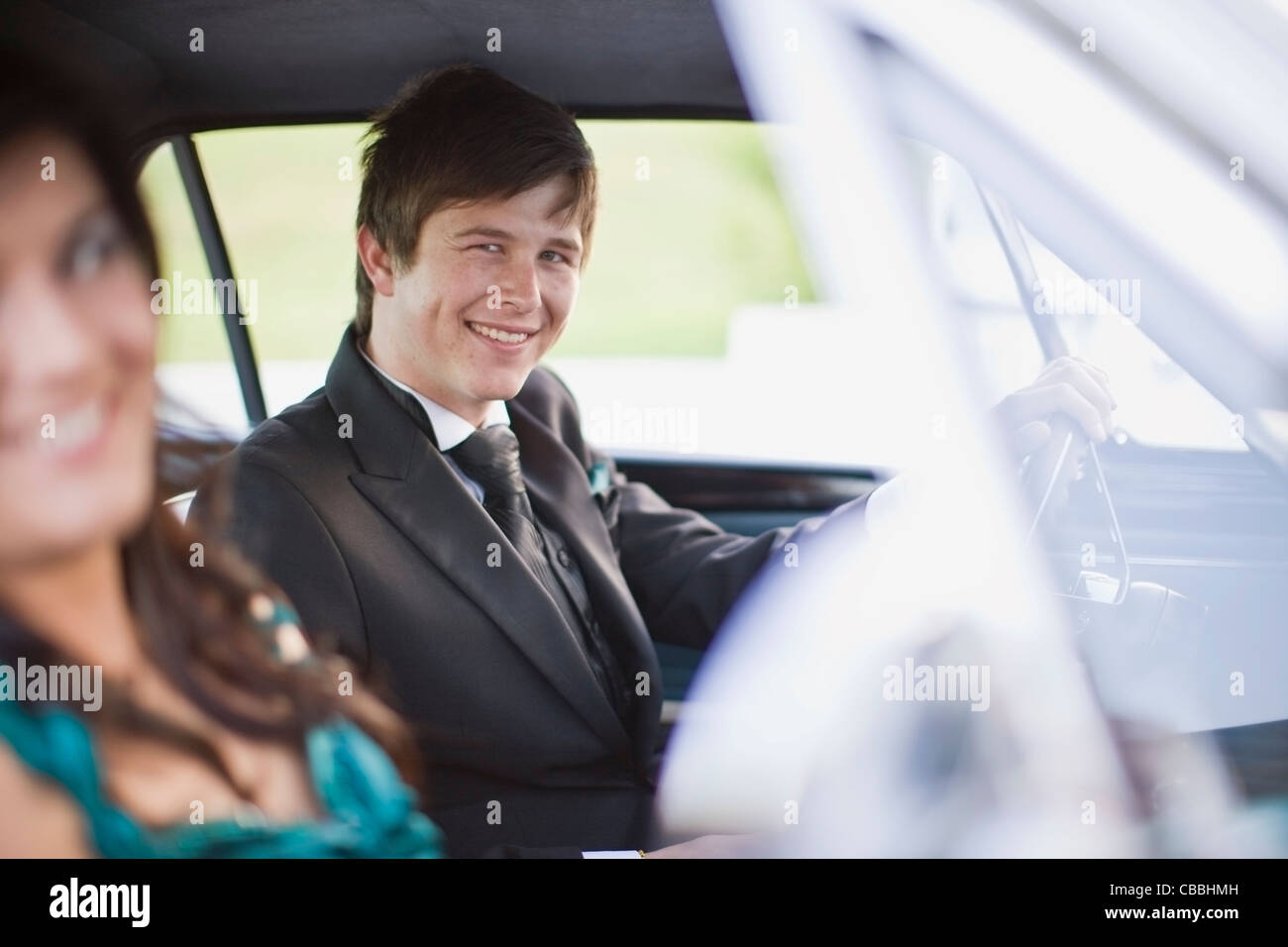 Gli adolescenti la guida auto in abbigliamento formale Immagini Stock