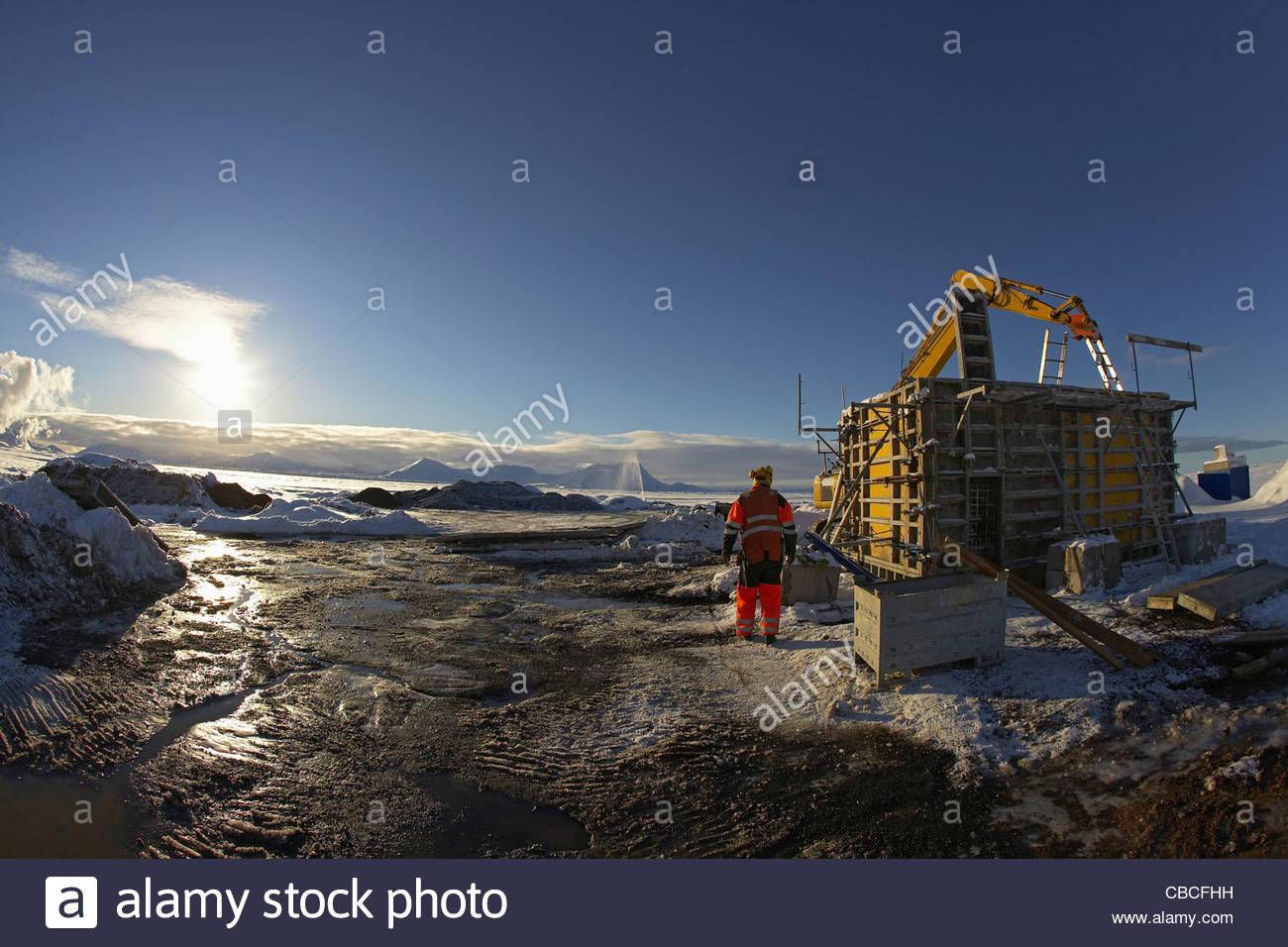 Lavoratori che si affaccia su sito in costruzione Immagini Stock