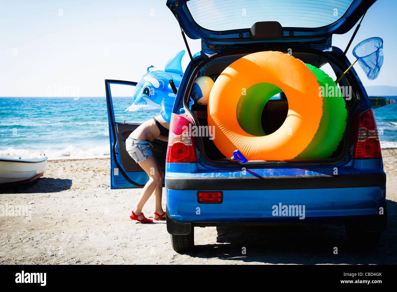 La donna lo scarico di giocattoli da spiaggia da auto Immagini Stock