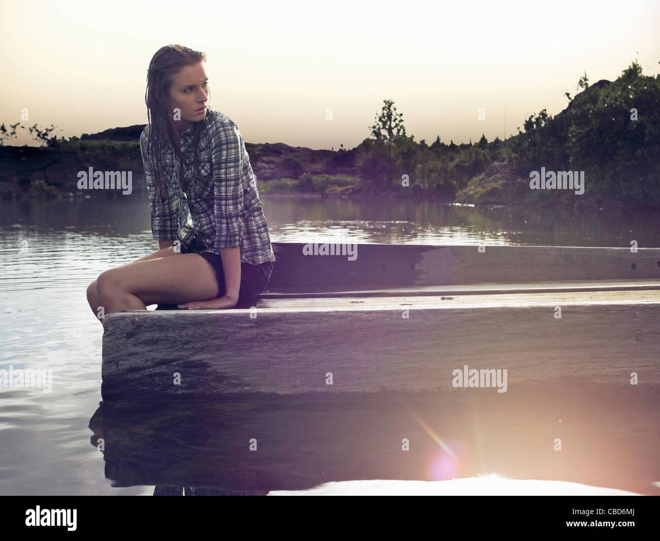 Donna seduta sul dock dal lago Immagini Stock