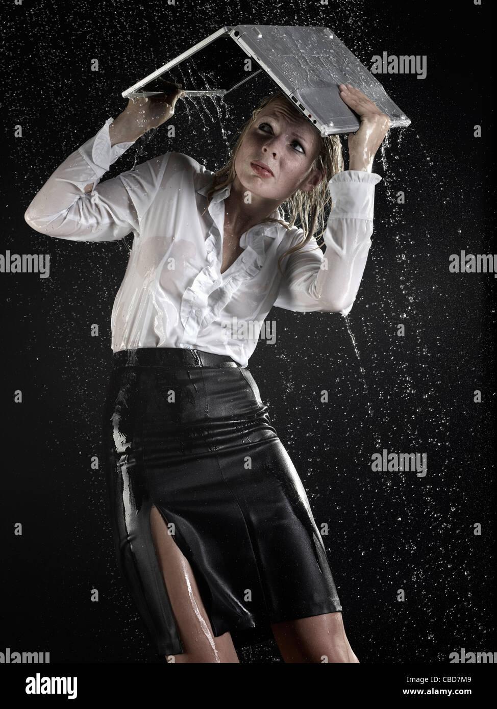 Imprenditrice sotto il computer portatile in caso di pioggia Immagini Stock