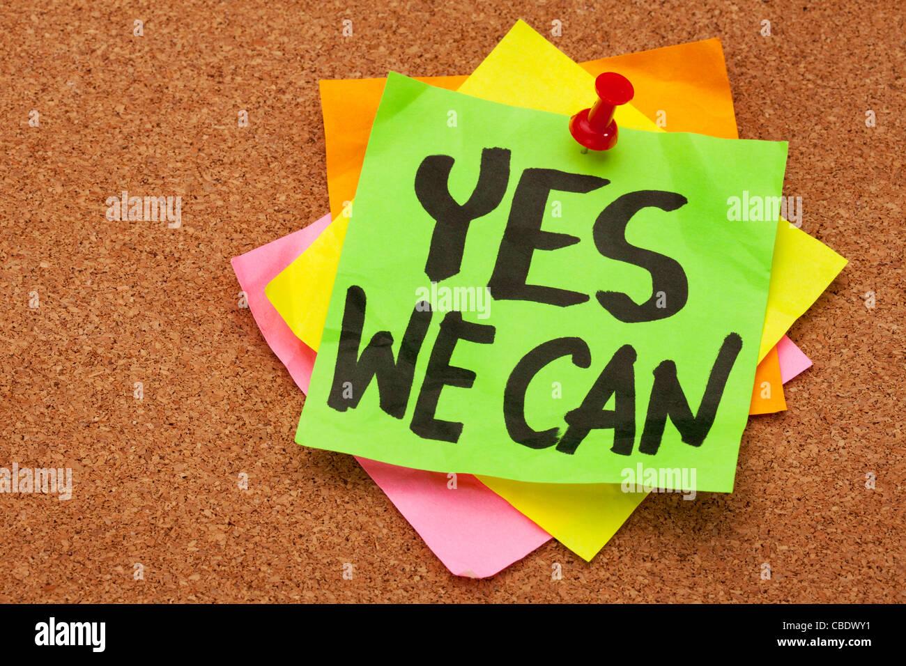 Yes We Can - slogan motivazionale su una pila di foglietti adesivi postato sul sughero bulletin board Foto Stock
