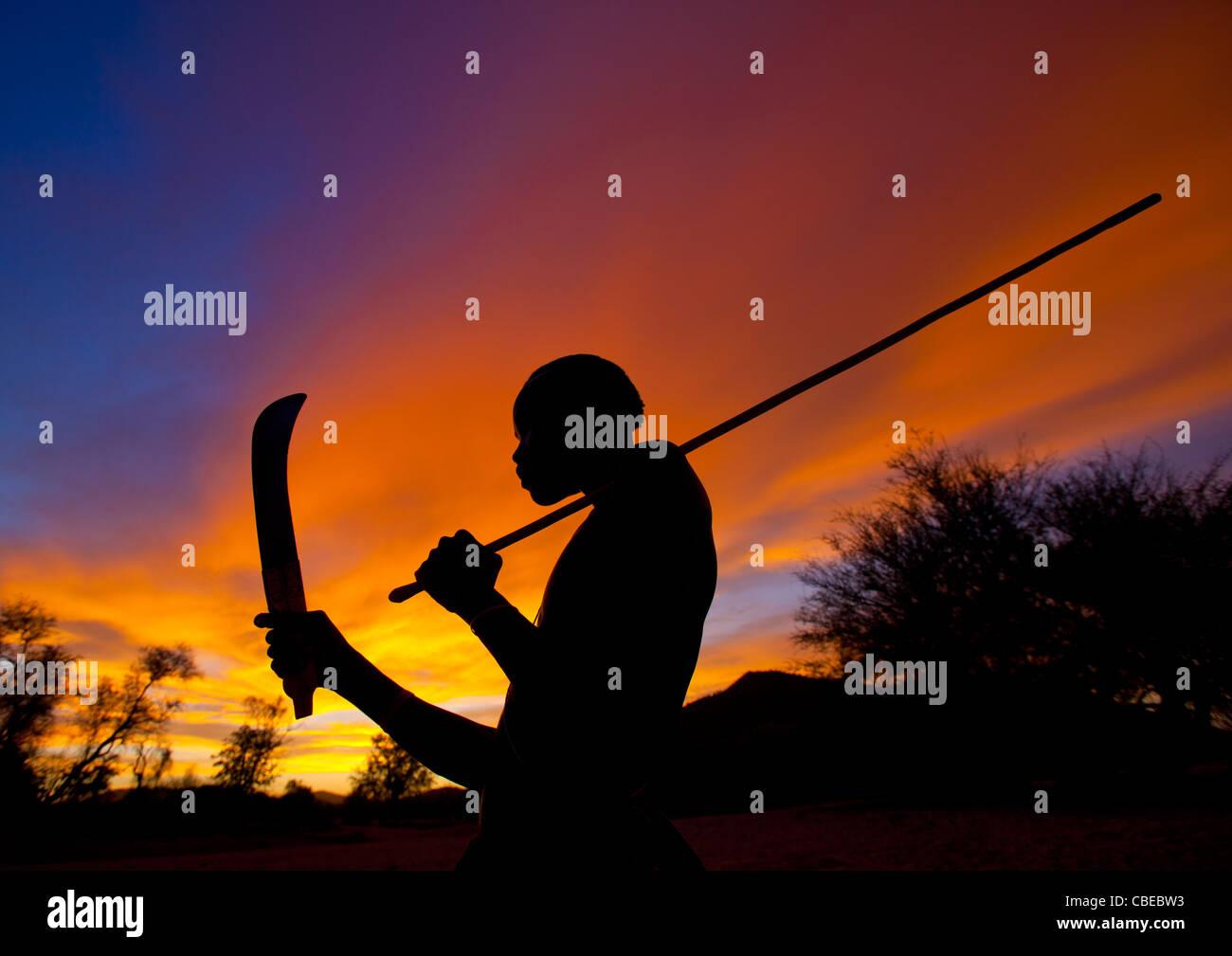 Mucubal ragazzo con coltello Omotungo al tramonto, Area Virie, Angola Immagini Stock