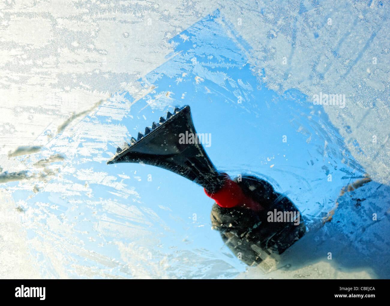 La raschiatura di ghiaccio da un parabrezza di automobile, vista dall'interno. Foto Stock