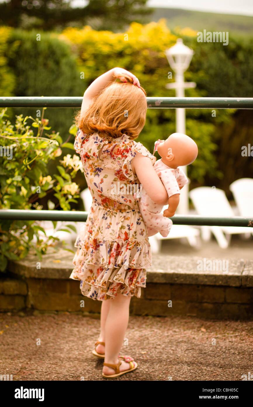 Parte posteriore di una bambina di età compresa tra i 5, tenendo in mano una bambola, guardando sopra un giardino Immagini Stock