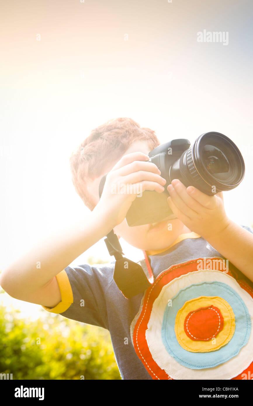 Un giovane ragazzo di età compresa tra i 7, utilizzando una fotocamera reflex digitale in un giardino soleggiato. Immagini Stock