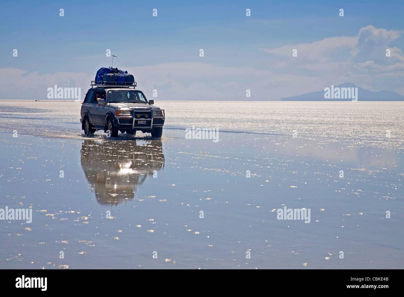 La trazione su quattro ruote a veicolo in marcia sulla distesa di sale Salar de Uyuni, Altiplano in Bolivia Immagini Stock