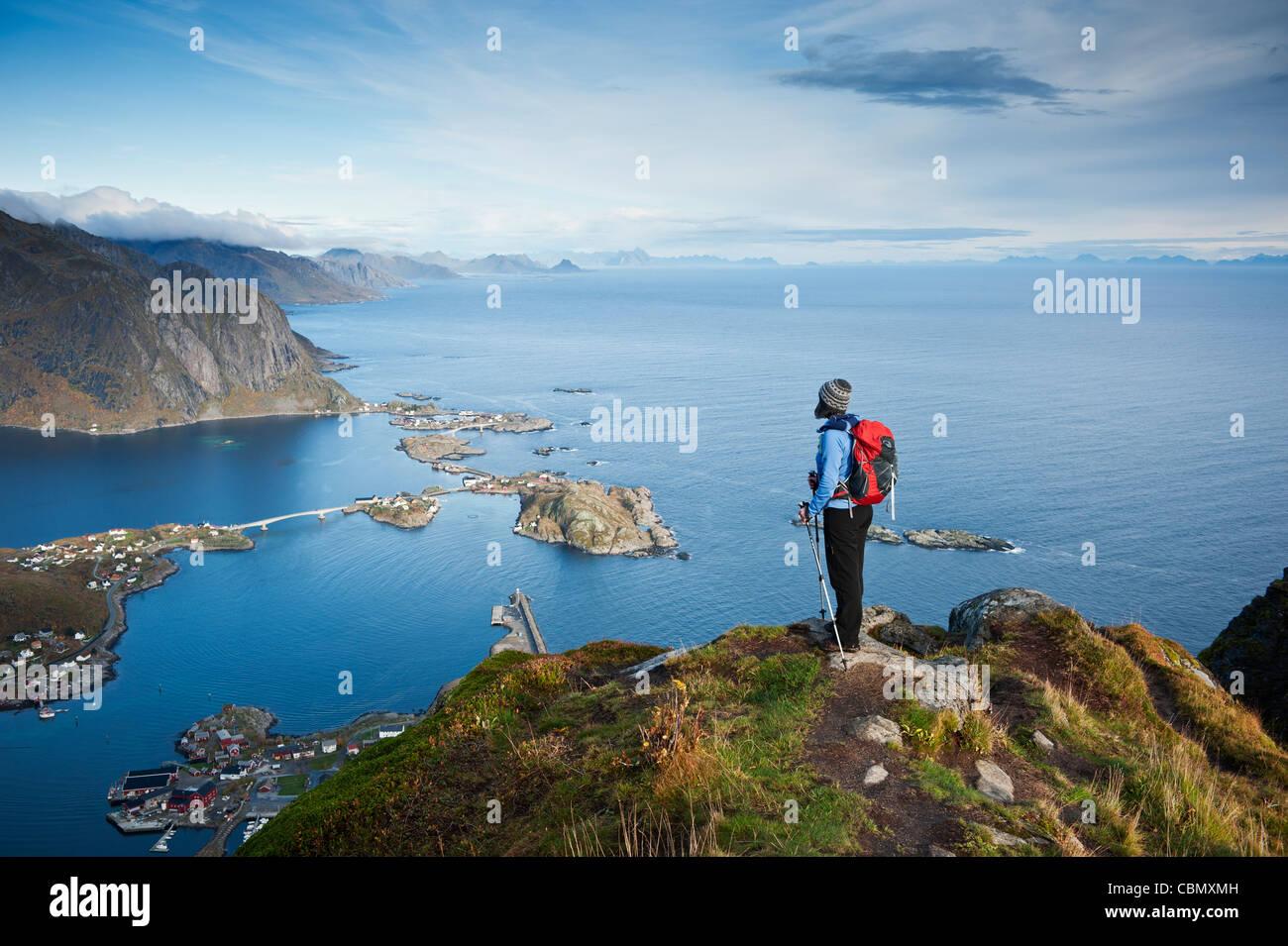 Escursionista femmina gode di una vista spettacolare sulle montagne e fiordi da Reinebringen, isole Lofoten in Norvegia Immagini Stock