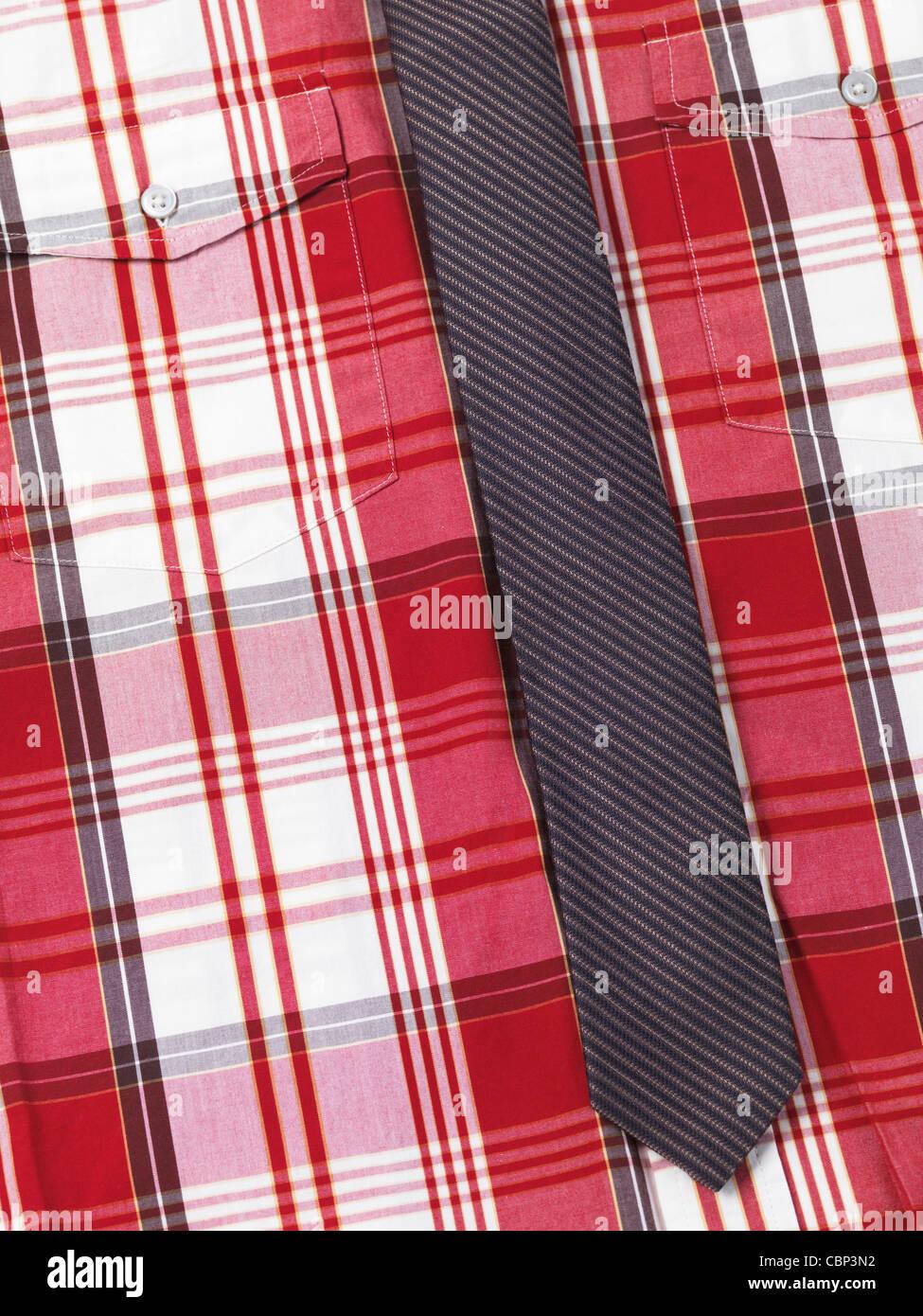 Primo piano di una mens fantasia tartan rosso maglia con un sottile striata cravatta Immagini Stock