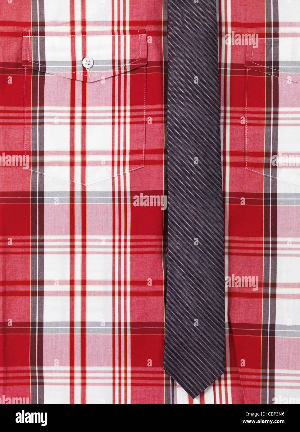 Primo piano di una mens fantasia tartan rosso maglia con un magro striata cravatta immagine di sfondo Immagini Stock