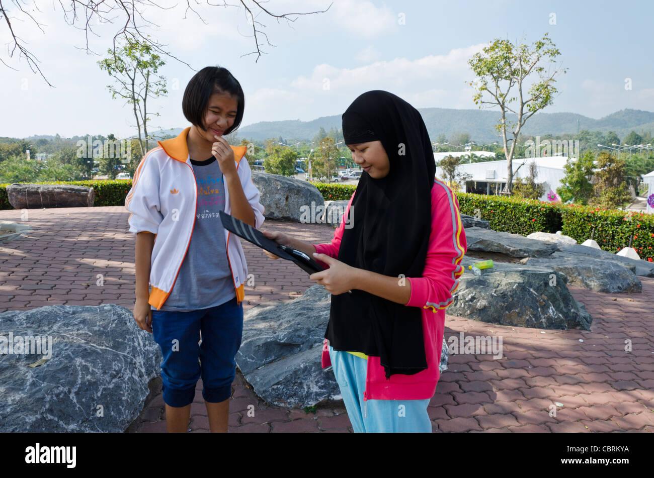 Sorridente musulmano Thai ragazza adolescente indossando lunga testa nera sciarpa guarda le foto sul suo iPad con Foto Stock