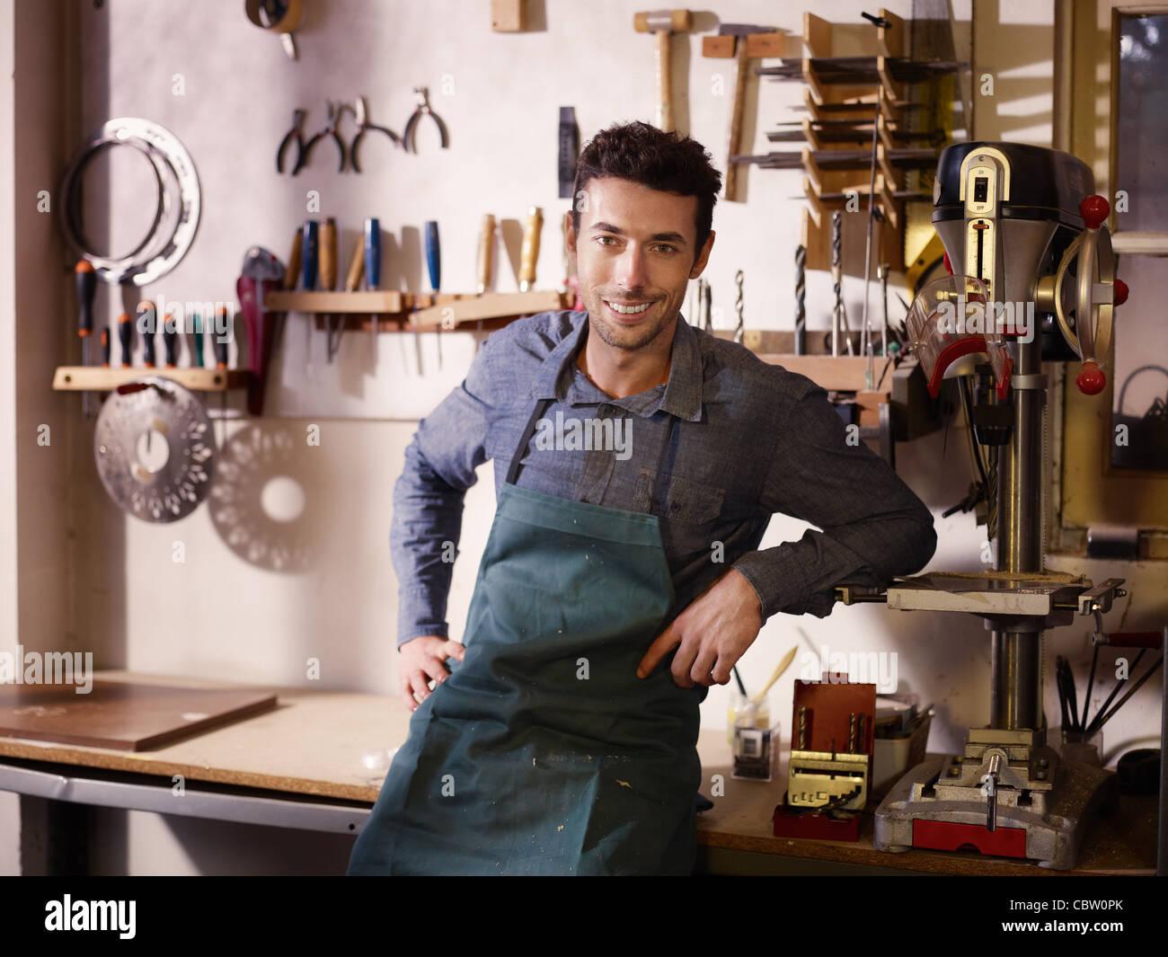 Ritratto di adulto uomo italiano al lavoro come artigiano in negozio con strumenti in background Immagini Stock