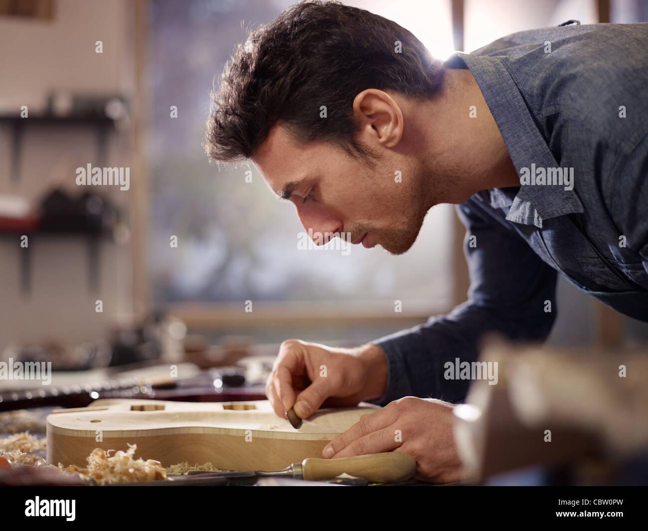 Metà uomo adulto a lavorare come artigiano in workshop italiano con le chitarre e strumenti musicali, levigatura Immagini Stock