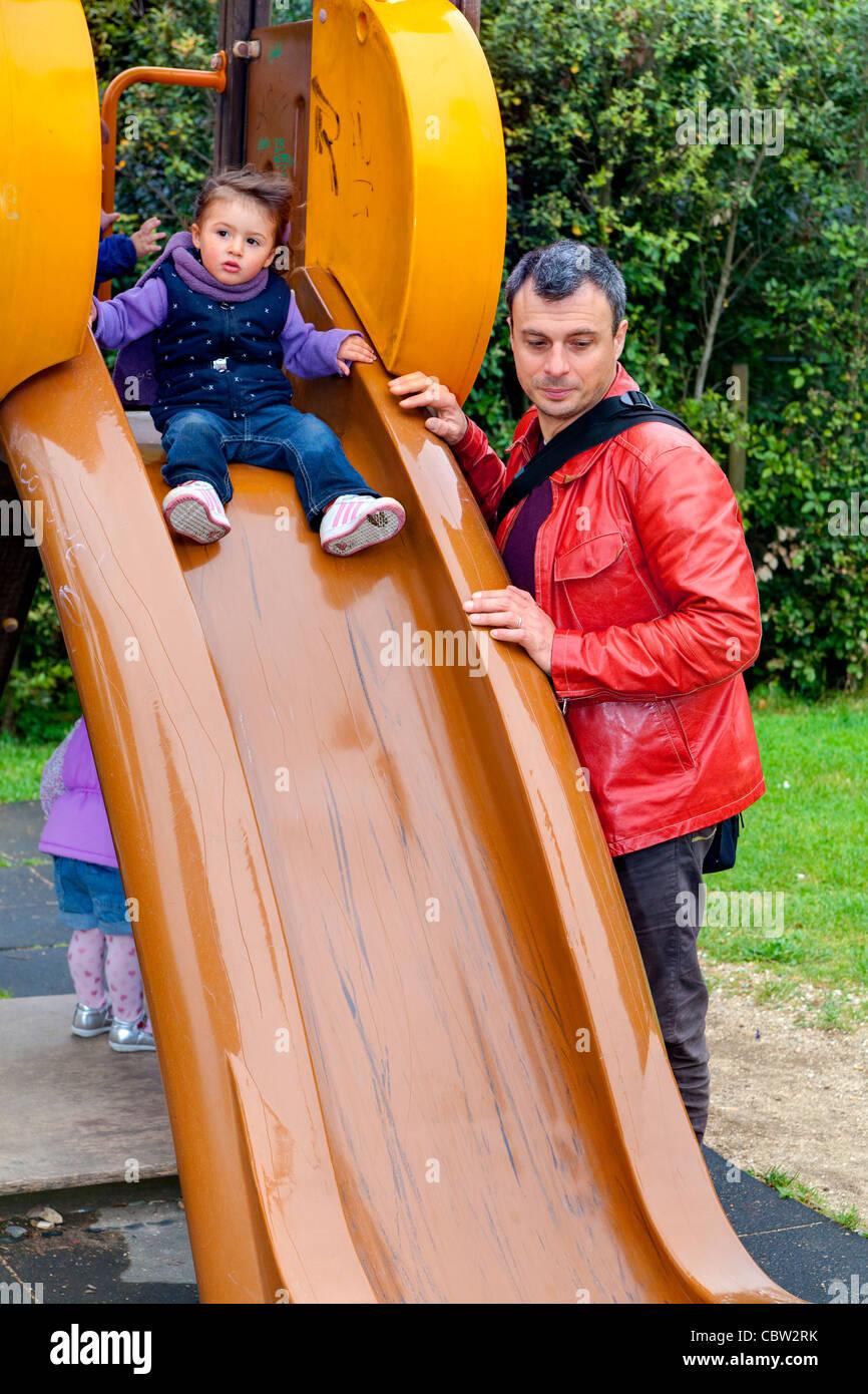 Padre e figlia su un parco giochi slitta Immagini Stock