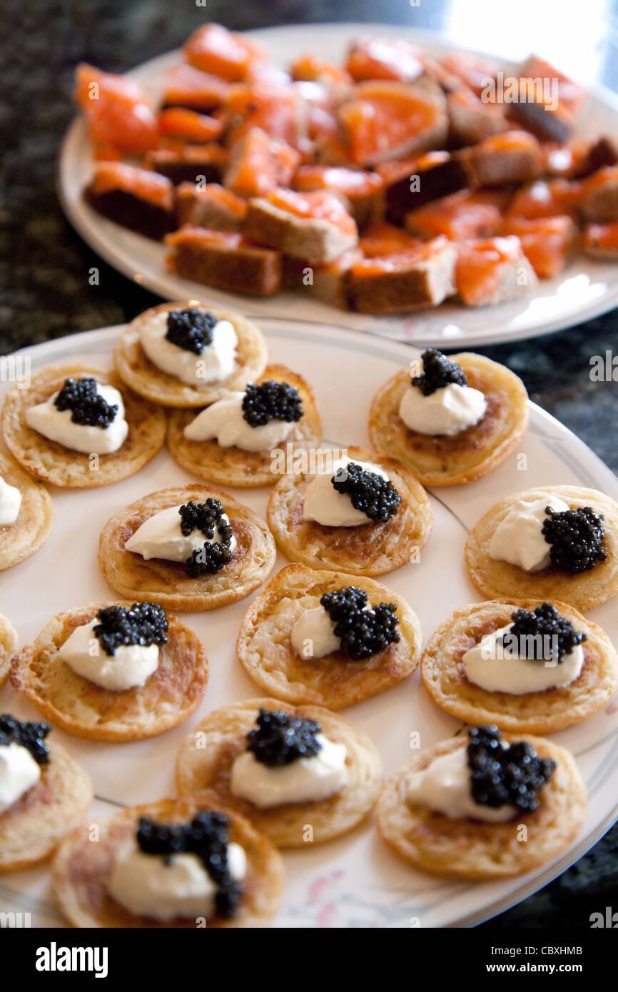 Blinis con panna acida e caviale con salmone affumicato su pane , Natale food UK Immagini Stock