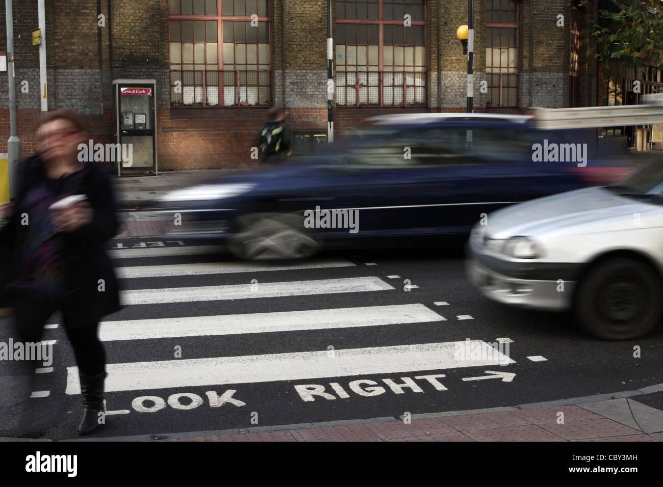 Accelerando il traffico attraverso una zebra crossing a Londra dopo una femmina aveva attraversato la strada Immagini Stock