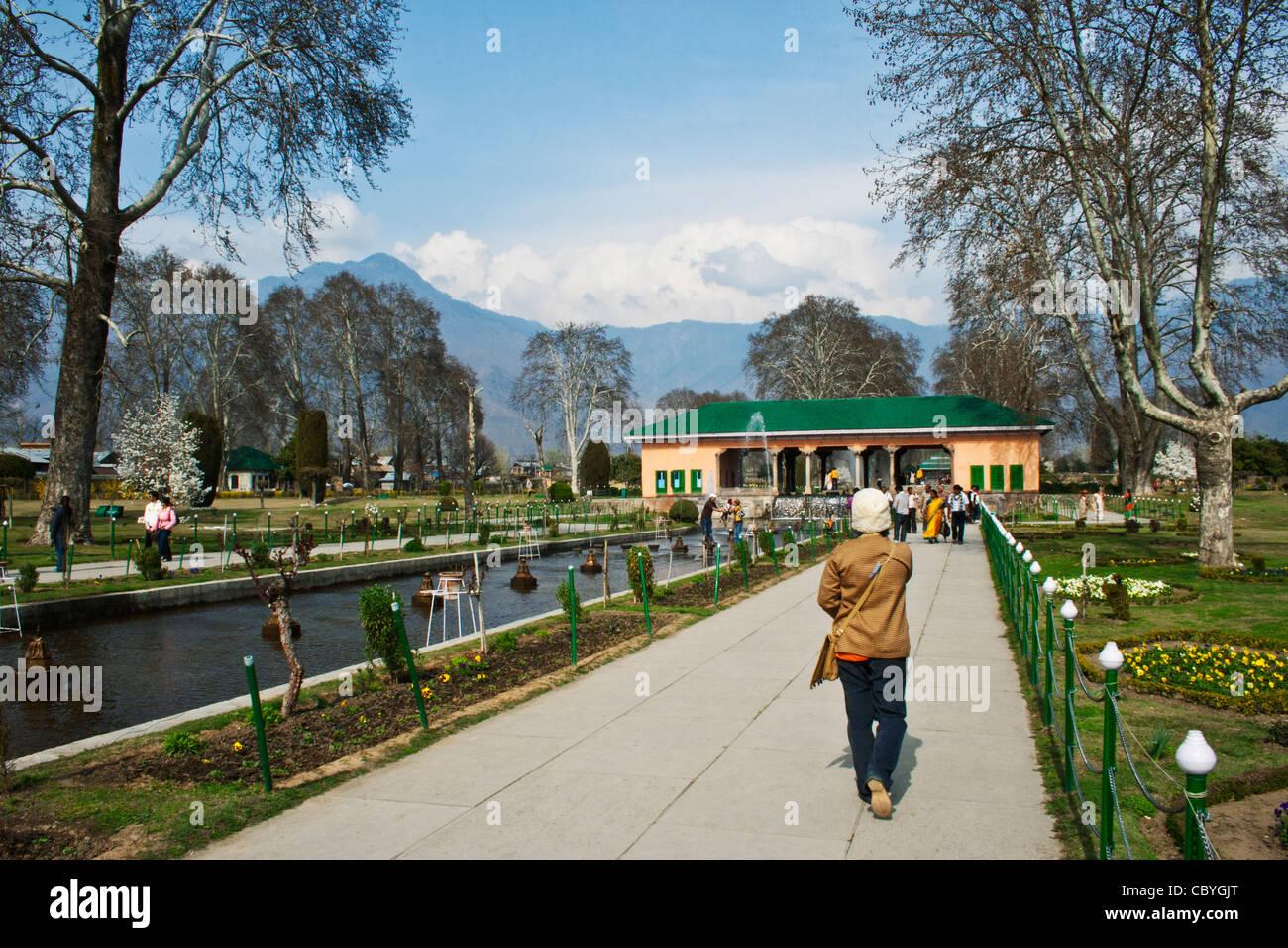 Un turista passeggiate fino alla passerella in il giardino di Mughal in Srinagar Kashmir, India Foto Stock