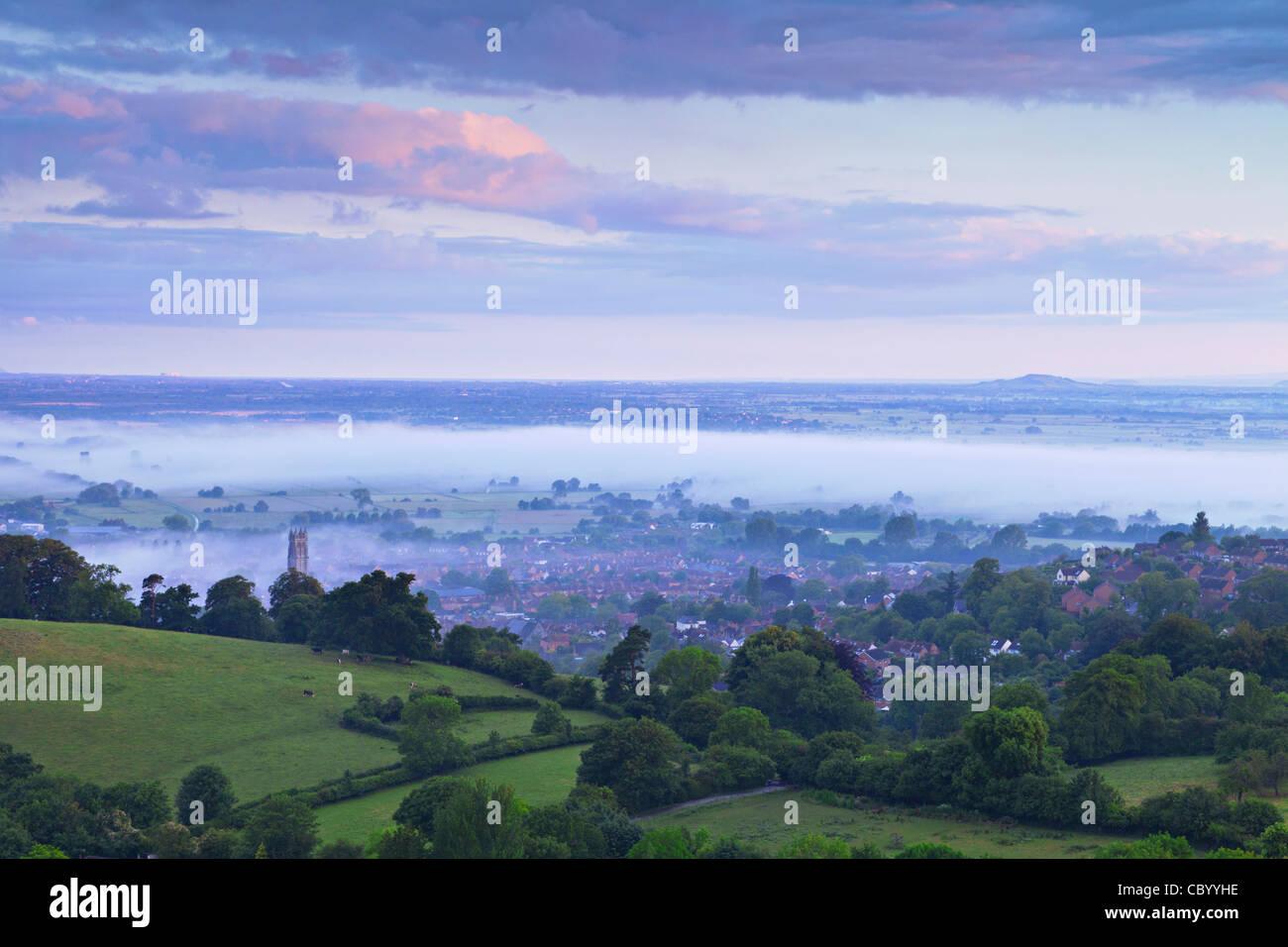 La città di Glastonbury e i livelli di Somerset e avvolto nella nebbia, da Glastonbury Tor, in pre-alba luce. Immagini Stock