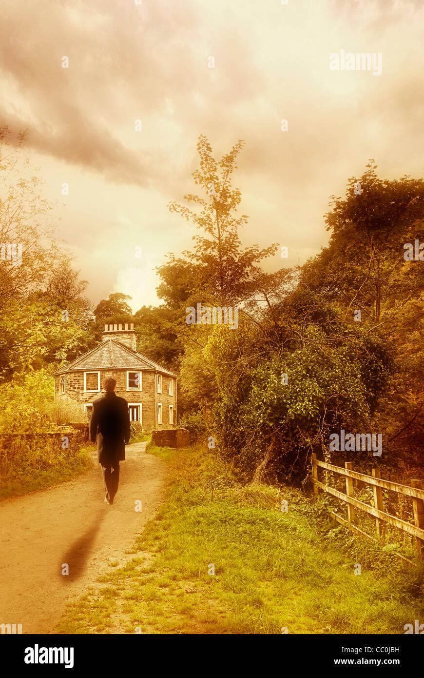 Uomo che cammina verso la casa di campagna Immagini Stock