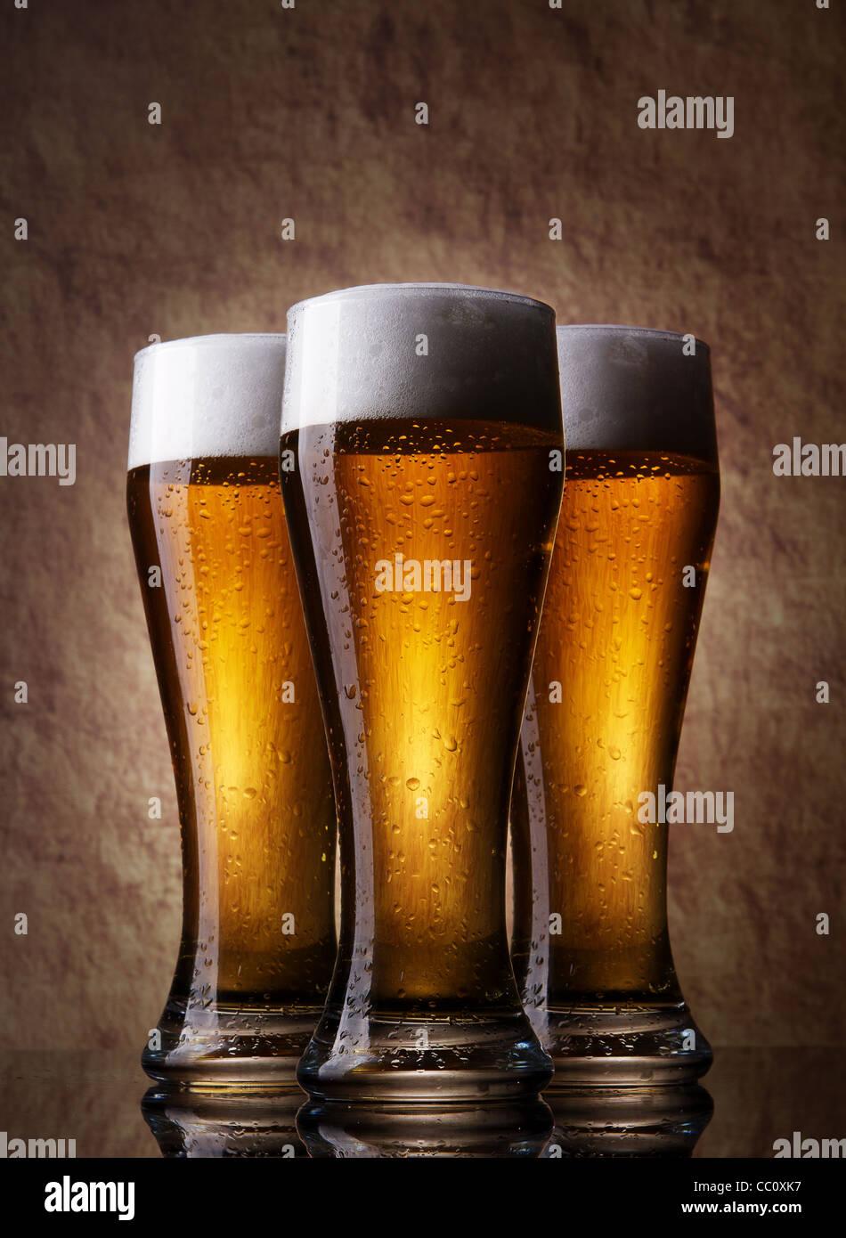 Tre birra fredda in vetro su una antica pietra Immagini Stock
