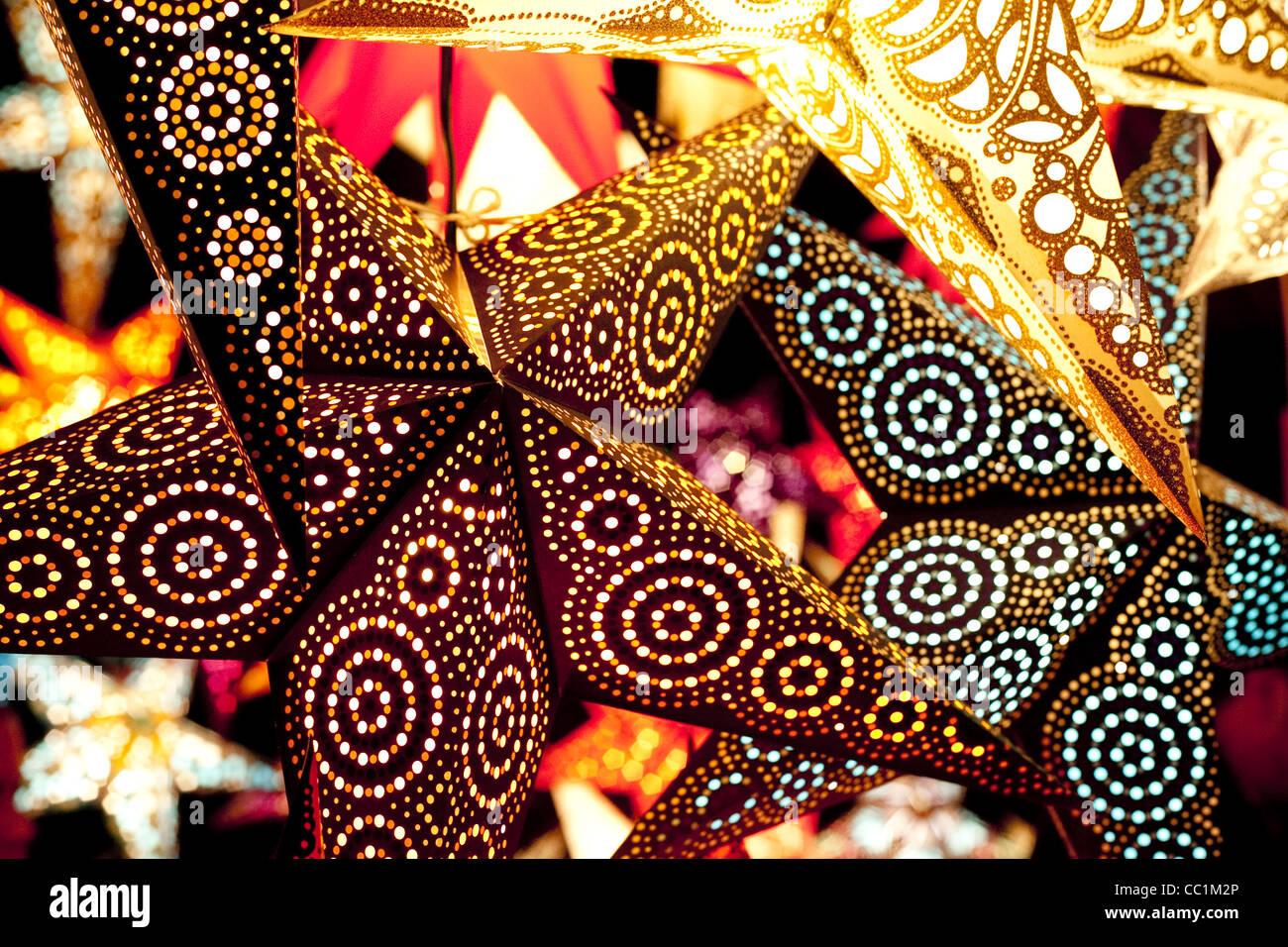 Luminosi colorati e dinamici illuminato di stelle di carta appeso in un mercato di Natale a Monaco di Baviera, Germania. Immagini Stock