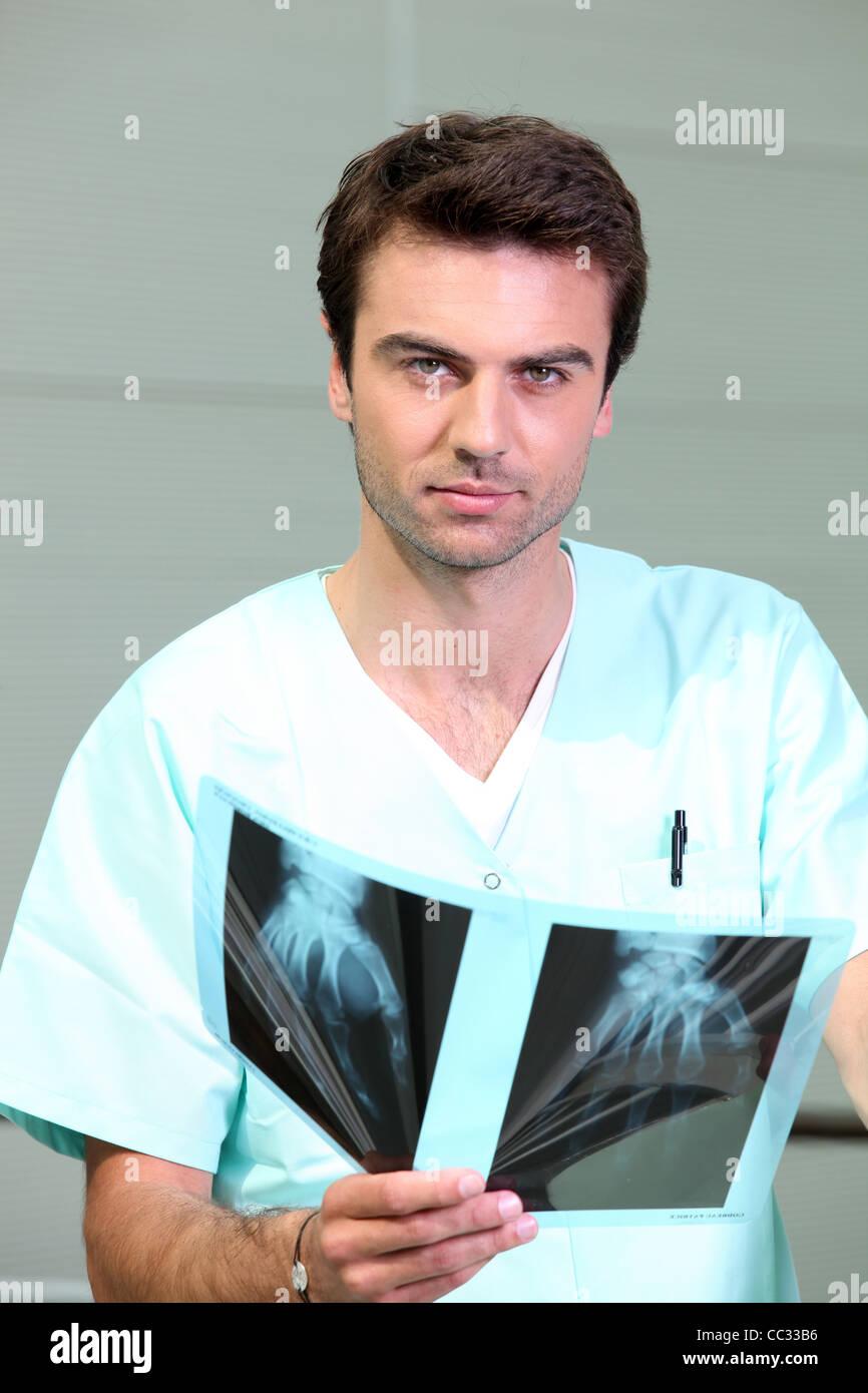 Medic in scrubs guardando i raggi x di una mano Immagini Stock