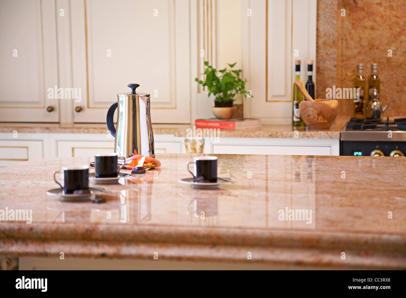 Cucina interno con caffettiera e tazze su un marmo Isola per ...