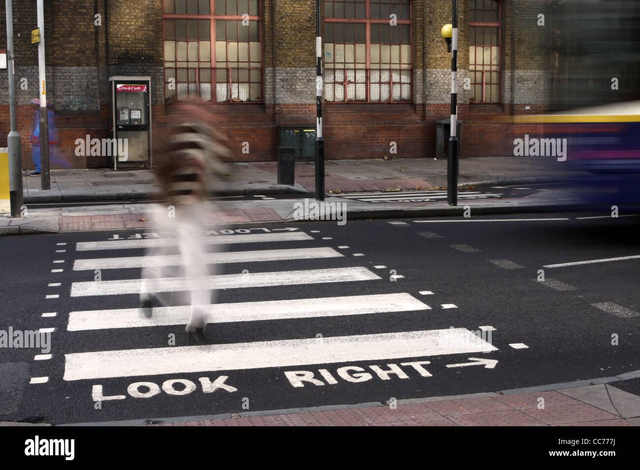 Una figura sfocata passeggiate attraverso una zebra crossing in Londra Foto Stock