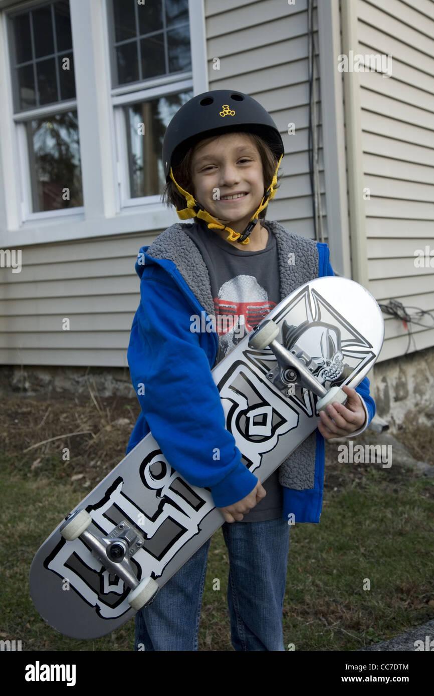 Sette anni di vecchio ragazzo con il suo skateboard in Darien, CT. Immagini Stock