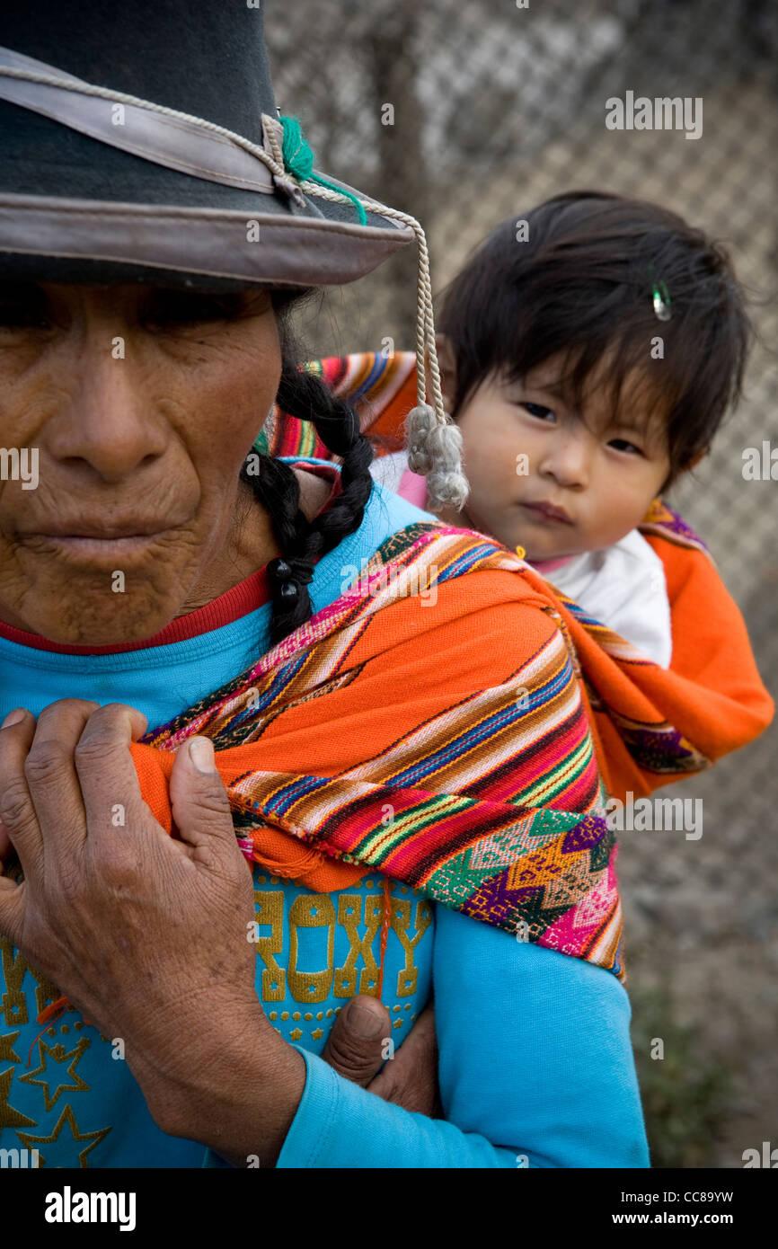 Una donna che porta un bambino sulla schiena in una delle baraccopoli di Lima, Perù, Sud America. Immagini Stock