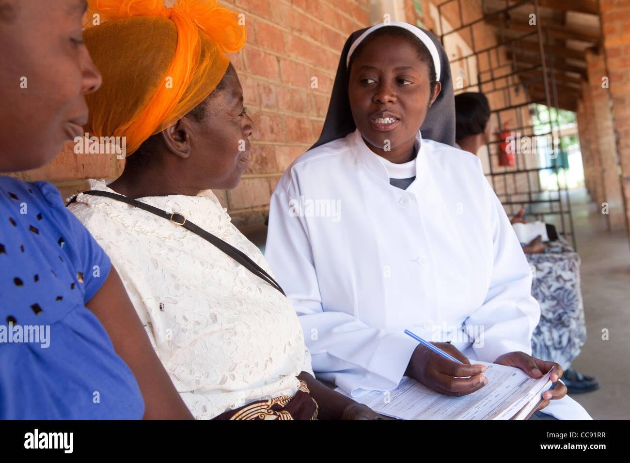 Un operatore sanitario professionale si consulta con i pazienti a un romano ospedale cattolico di Ibenga, Zambia, Sud Africa. Foto Stock