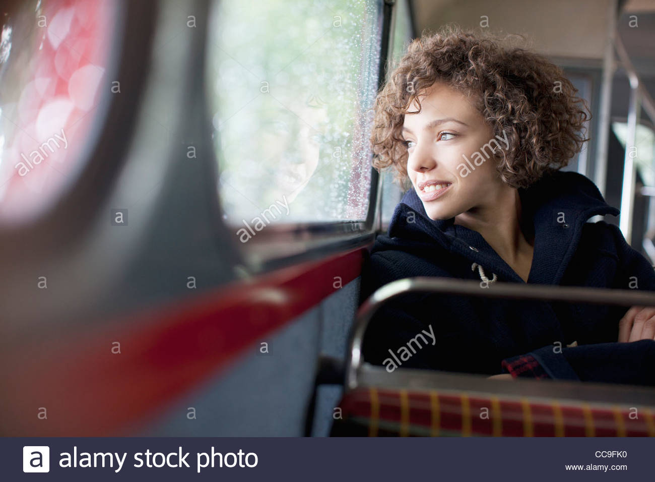 Donna sorridente bus di equitazione Immagini Stock