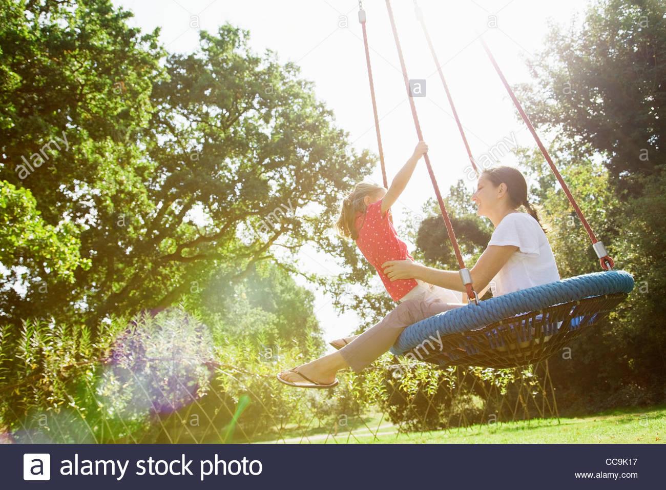 Madre e figlia su altalena nel soleggiato parco Immagini Stock